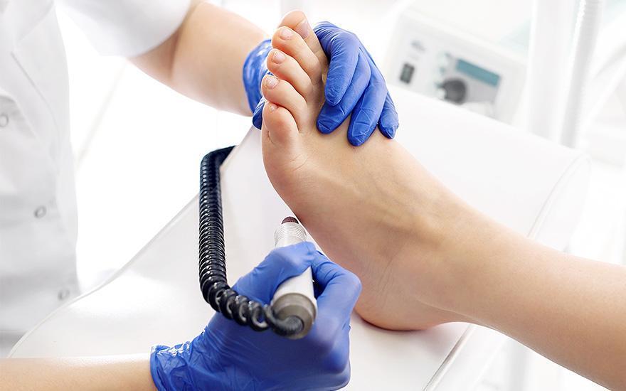 Lekarz trzymający urządzenie przy stopie pacjenta